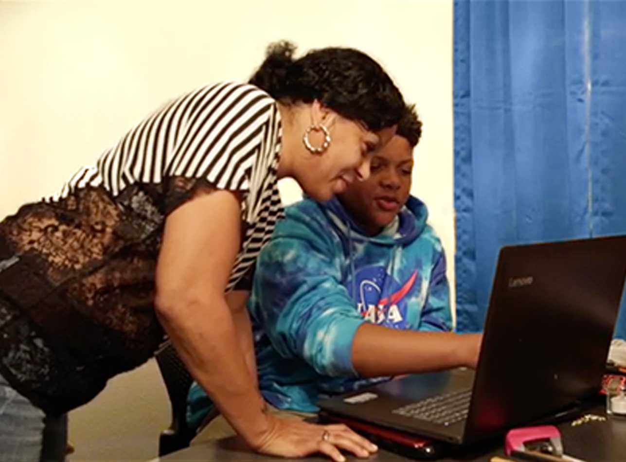 Woman and boy working on a computer.